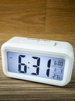 木製のテーブルに白い目覚まし時計のデジタル数字。 Premium写真