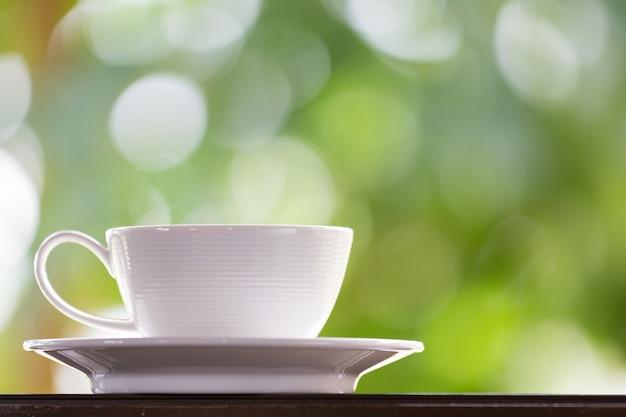 흰색 커피 컵은 창 근처에 있습니다.