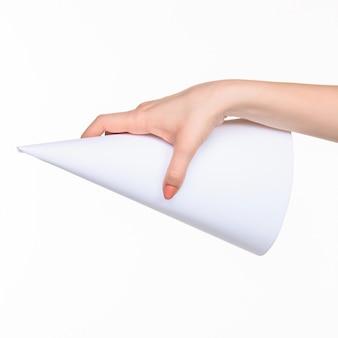 오른쪽 그림자가있는 흰색 배경에 여성 손에있는 소품의 흰색 원뿔