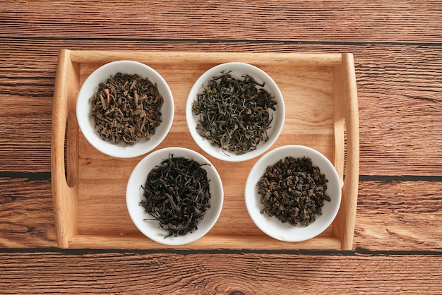 木製の背景に順番に乾いたお茶の品揃えの白いお椀