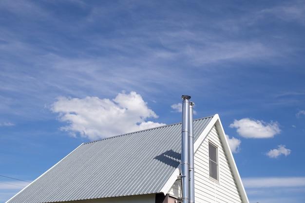 Белая металлическая крыша коттеджа с трубой из нержавеющей стали на фоне голубого неба. крыша сделана из металлического оцинкованного профиля.