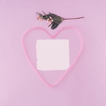 Белая бумажная карта и розовая форма сердца на пастельно-фиолетовом фоне. любовное письмо валентина.