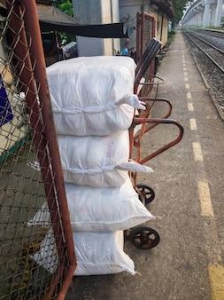 トロリーの白い小包バッグは、市の駅のホーム近くの貨物列車に出荷する準備ができています。コピースペースの正面図です。