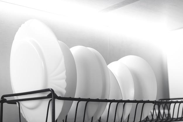흰색 접시는 주방의 현대적인 인테리어 배경 사진에 있는 건조기에 납작하게 쌓여 있습니다.