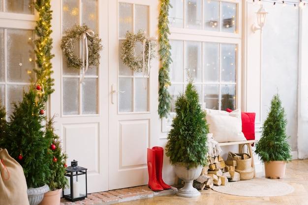 Белый частный дом украшают маленькие елочки и фонарики, мешок с подарками.