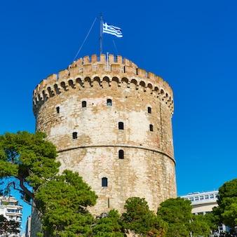 Белая башня с греческим флагом в салониках, греция