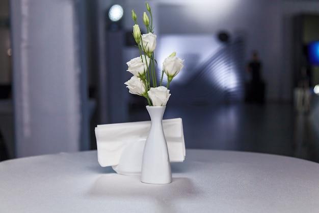 흐린 배경에 냅킨 홀더 근처 테이블에 꽃이 서 있는 흰색 꽃병.