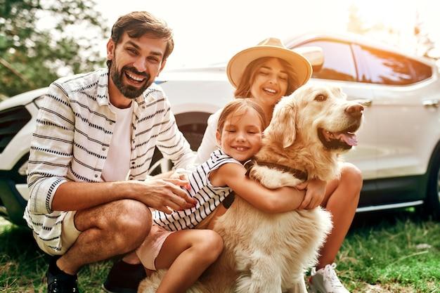 Вся семья приехала на природу на выходные. мама и папа с дочерью и собакой лабрадором стоят возле машины. отдых, путешествия, туризм.