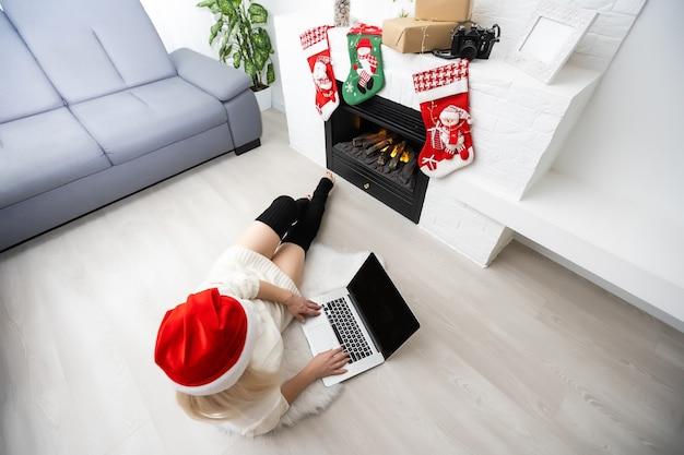 ワンタッチで全世界。ノートパソコンで作業し、クリスマスの背景を笑顔で美しい若いブロンドの髪の女性のクローズアップ