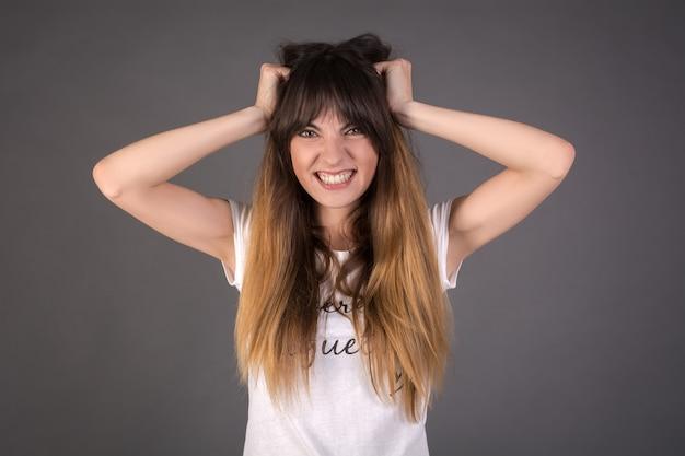 Злая девушка рвет себе волосы.
