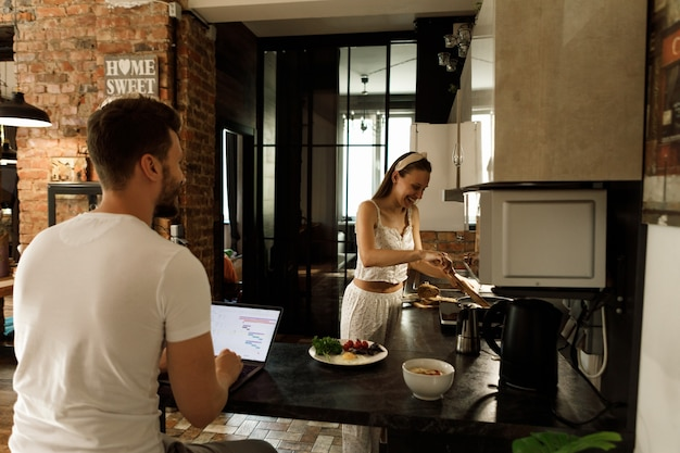 妻は台所で料理をし、夫は働きます。台所で話している夫婦。