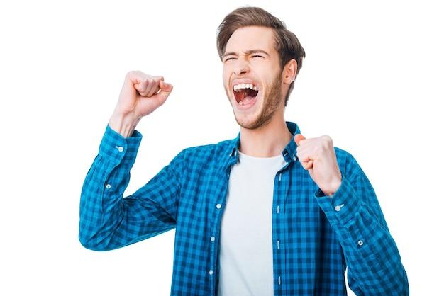 Победа у меня в кармане. взволнованный молодой человек держит руки поднятыми и выражает позитив