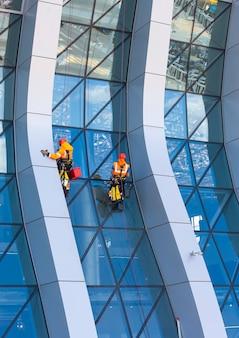 ガラスファサードのモダンな超高層ビルに取り組んでいるウィンドウクリーナー
