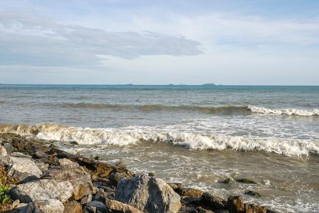Ветреные волны ударяют о скалы у моря.