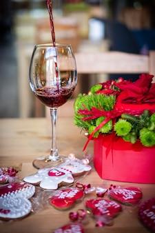 와인을 유리 잔에 붓습니다. 발렌타인 데이를위한 빨간 꽃다발