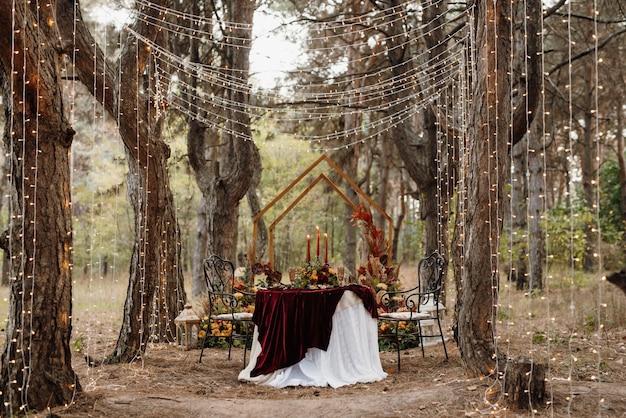 レストランの宴会場にある新婚夫婦のワイン幹部会は、キャンドルと緑の植物で飾られ、藤が天井からぶら下がっています