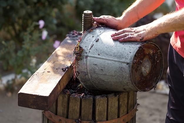 ワインメーカーは原材料をプレスに注ぎます。伝統的なイタリアワインの生産、ブドウの粉砕。