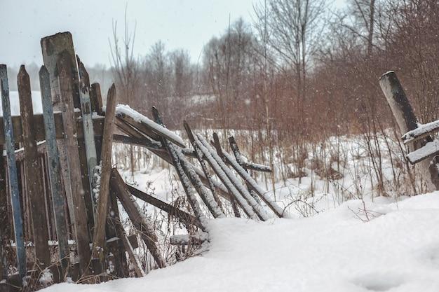 Зимний пейзаж, сломанный забор в снегу