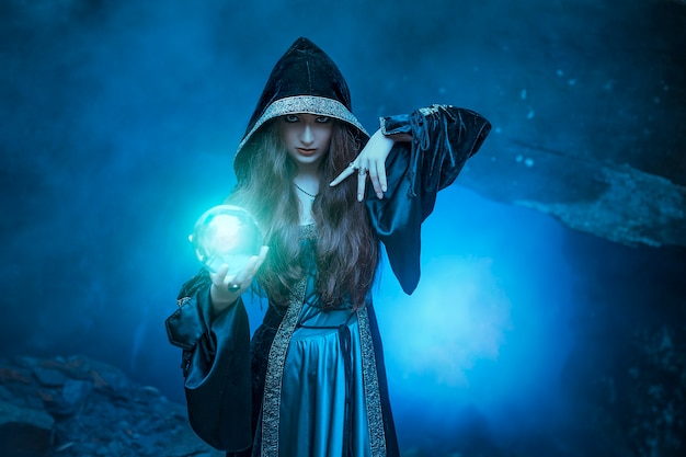 그녀의 손에 마법의 공을 가진 마녀는 동굴에 영혼을 유발
