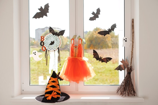 魔女のカーニバルドレスが窓にぶら下がっていて、コウモリ、帽子、ほうきが窓辺にあります