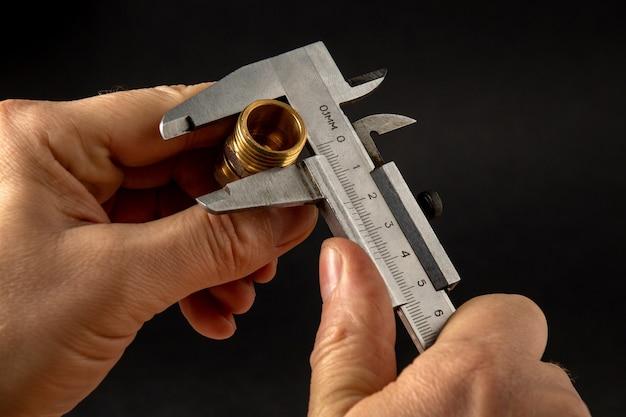 마법사는 캘리퍼를 사용하여 황동 피팅의 크기를 측정합니다.