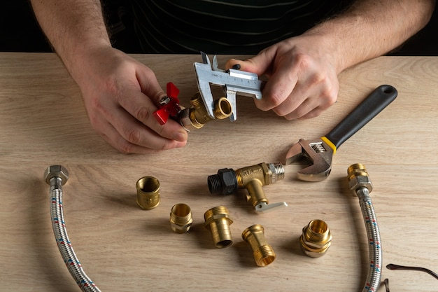 ウィザードは、水道管またはガス管を接続する前に、キャリパーを使用して継手のサイズを測定します。