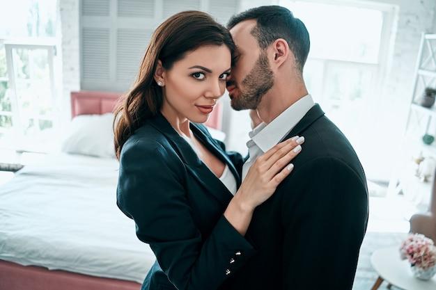 スーツを着た女性と男性が部屋に抱きしめます