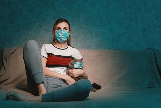 テレビの前のソファに座っている女性と猫は、両方とも保護用の医療用マスクに入っています