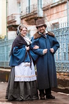 Женщина и мужчина в винтажных костюмах. люди в ретро-платьях. гуляя по улице