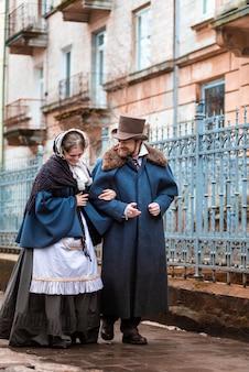 ヴィンテージのスーツを着た女性と男性。レトロなドレスを着た人。通りを歩く