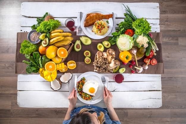 Женщина за обеденным столом с натуральными продуктами, вид сверху
