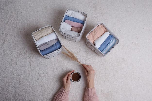 Женщина аккуратно складывает одежду и складывает ее в корзины и коробки. минимализм в скандинавском стиле.