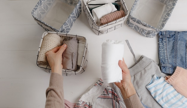 Женщина аккуратно складывает одежду и складывает ее в корзины и коробки.