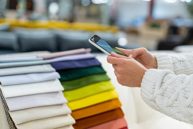 Женщина выбирает ткань на диване, фотографируя образцы ткани по телефону.