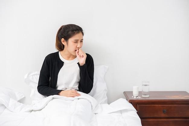 여자는 기침을하고 손으로 입을 가리고 침대에 앉았다.