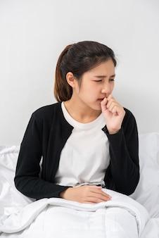 女性は咳をして口を手で覆い、ベッドに座った。