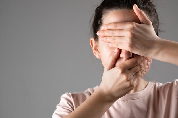 女性は手で口と目を覆っている。