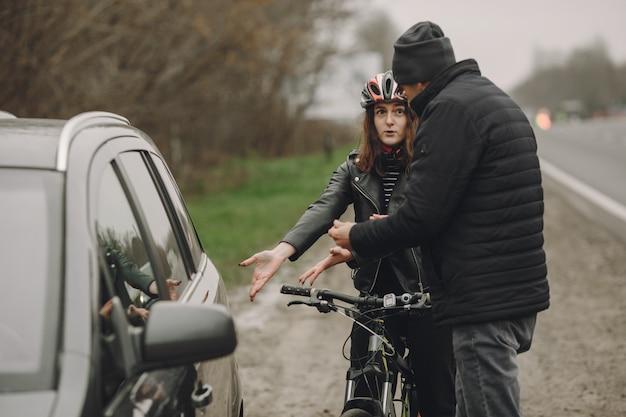 여자는 차에 추락했습니다. 헬멧에 소녀입니다. 사람들은 사고를 놓고 다투고 있습니다.