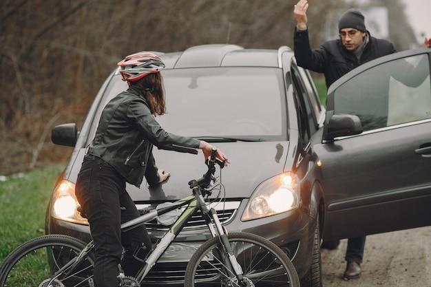 女性は車に激突した。ヘルメットをかぶった少女。人々はその事故について喧嘩している。