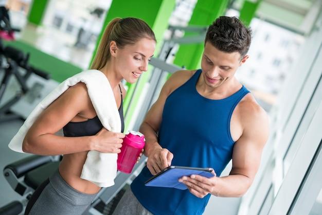 Женщина обсуждает с фитнес-инструктором с планшетом