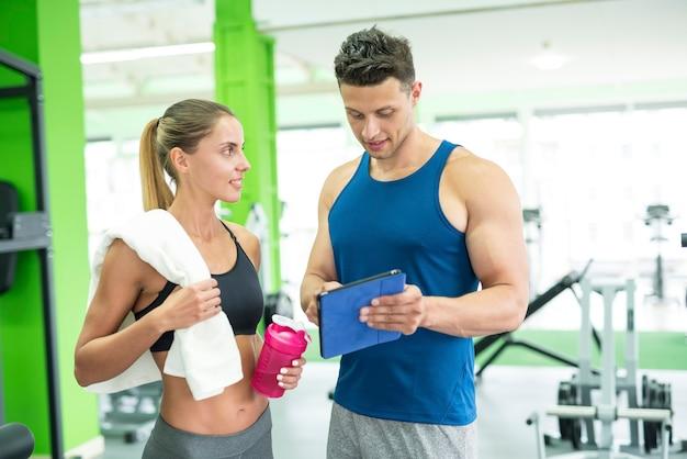 Женщина обсуждает с фитнес-инструктором