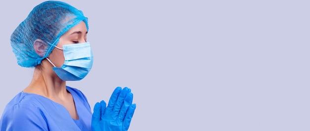 파란색 의료복을 입고 눈을 감고 마스크를 쓴 여의사가 환자의 빠른 쾌유를 기도하고 있습니다.
