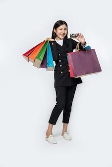 Женщина, одетая в темное, ходила по магазинам с кредитными картами и множеством сумок.