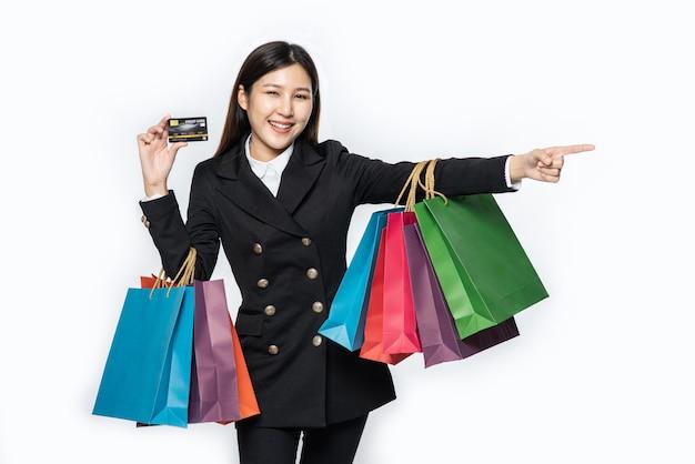 暗闇に身を包んだ女性は、クレジットカードとたくさんのバッグを持って買い物に行きました。