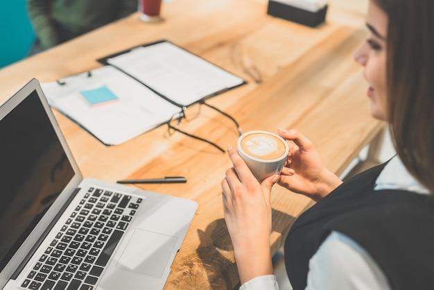 Женщина пьет кофе за рабочим столом