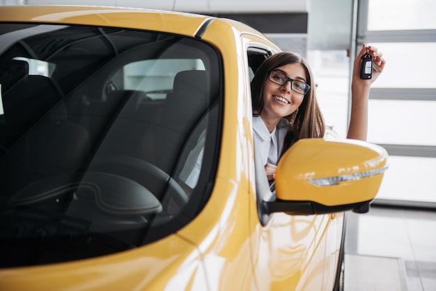 Женщина-водитель улыбается, показывая новые ключи от машины