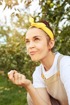屋外の庭でリンゴを摘みながら女性