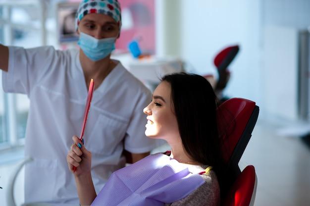 Женщина получает удовольствие от прекрасной работы стоматолога.