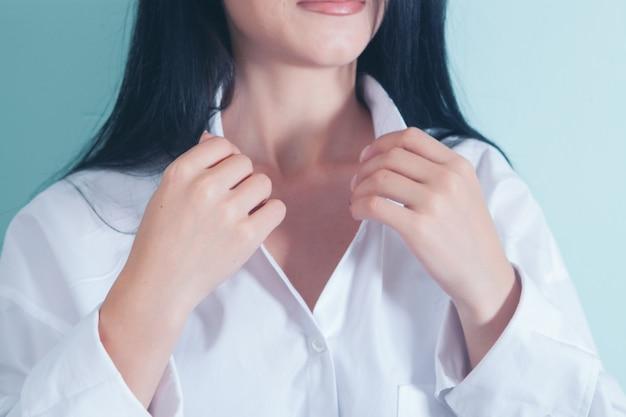 여자는 셔츠의 단추를 잠급니다