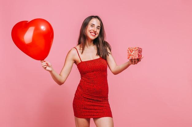 女性は贈り物とハートの入った箱を渡します。ピンクの壁